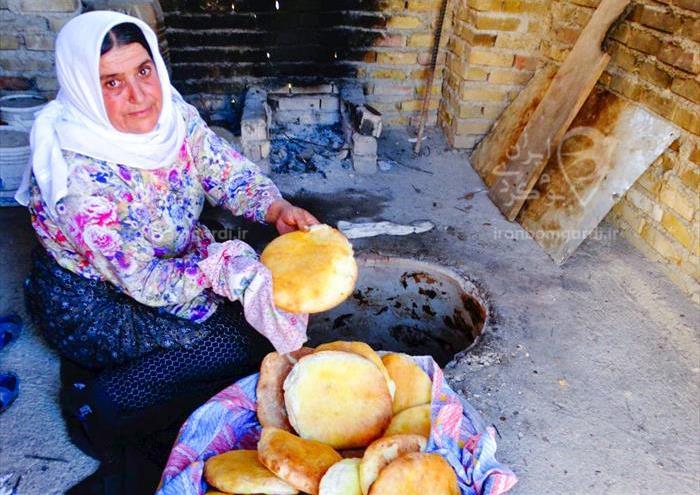 پختن نان تنوری به روش سنتی در اقامتگاه خانه مادر ب